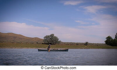 A lone man in a canoe paddles down an empty calm river in...
