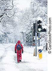 A lone man in red, walking through a snow-covered country lane