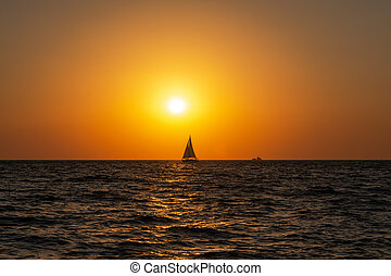 A lone sailboat at sunset. Atmospheric seascape with orange sun.