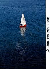 A lone white sail on a calm blue se