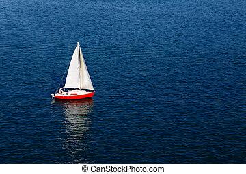 A lone white sail on a calm blue se - A lone white sail of a...