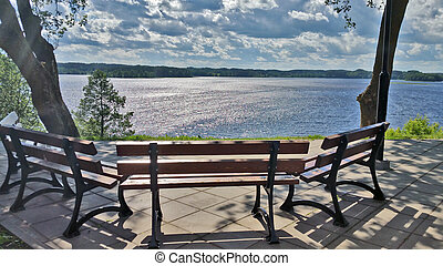 A lonely bench overlooking the lake, on a summer sunny day