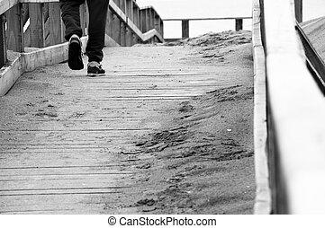 a lonely boy walking on a wooden bridge near the sea