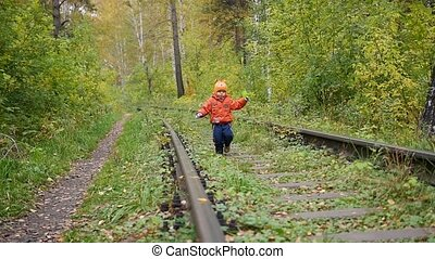 A lonely boy walking on the railroad tracks. Dangerous games and entertainment. Autumn day