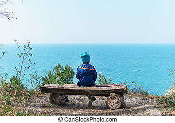 A lonely child is resting on a bench in the forest with a view of the sea.