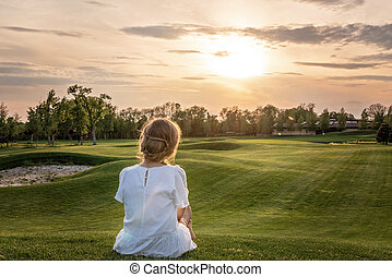 A lonely girl in a white dress sitting on golf course looking at sunset sunrise sun.