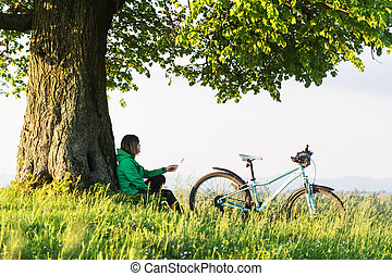 A lonely girl sits under a big old tree near a bicycle