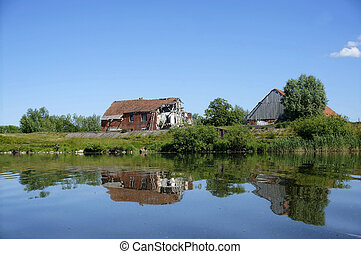 a lonely old house on the lake, the houses reflected in the lake surface of the lake, calm