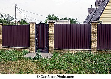 a long brown fence with a closed door of metal and brick outside in the green grass