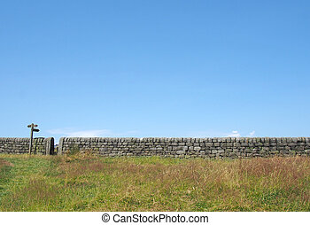 a long dry stone wall running along a grass covered summer meadow with bright blue sky and gate with old direction sign