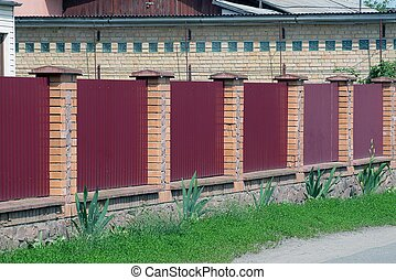 fence of red metal and brown bricks outside in green grass