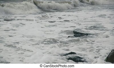 A long foamy wave rolls to shore slow motion