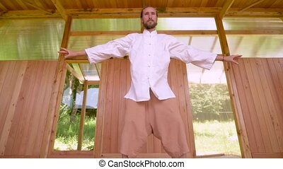 A long-haired Caucasian man in light and loose clothing practices qigong tai chi in a wooden practice room in summer. Slow movements harmony and calm.