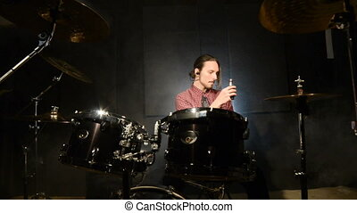 A long-haired drummer sitting behind a drum kit is hovering...