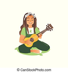 A long haired girl or a young beautiful woman sits on the grass and plays the guitar.