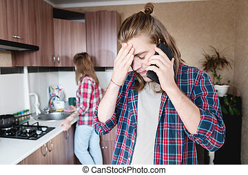 A long-haired man is upset talking on the phone or calling a food and drug delivery service home standing in the kitchen