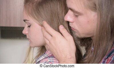 A long-haired young man hugs his girlfriend from behind, ...