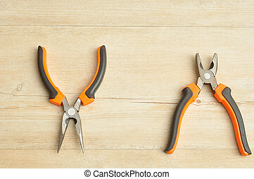 A long nose pliers and a pliers isolated on a wooden background
