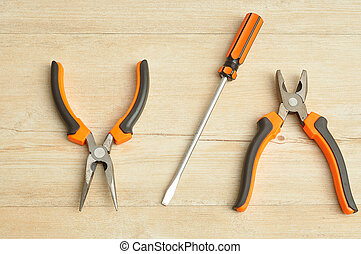 A long nose pliers, screw driver and a pliers isolated on a wooden background
