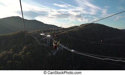 A long-shot of a unidentified man bungy jump off 207 m a ...