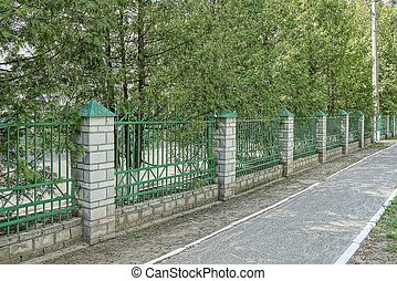 a long wall of green metal and white brick fence on the street