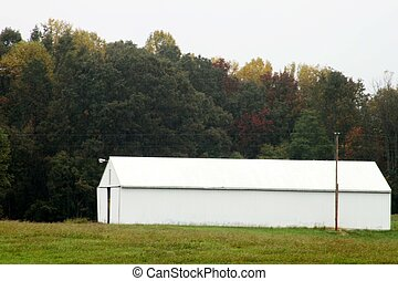 A Long white barn with trees