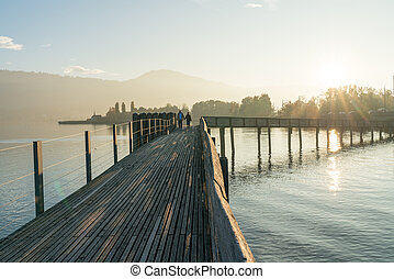 long wooden boardwalk pier over water in golden evening light with a mountain landscape and person silhouette in the background