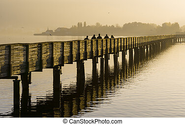 long wooden pier and boardwalk over Lake Zurich in golden evening light with silhouette of pedestrians and people walking and mountains in the background