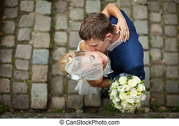 A look from above on the groom kissing bride's cheek tender