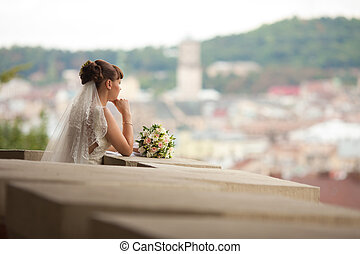 A look from afar on a thoughtful bride leaning on the balcony