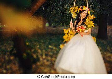 A look from afar on the fairy bride sitting on the swing full of autumn leaves
