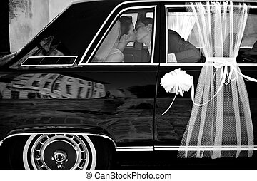 A look from afar on the wedding couple kissing in the limousine decorated with white laces