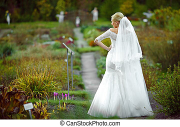 A look from behind on the elegant blonde bride standing on the path in the garden
