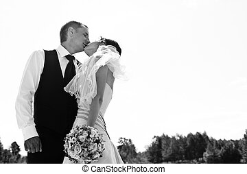 A look from below on the groom kissing a bride in a sunny day