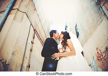 A look from below on the newlyweds kissing in the alley