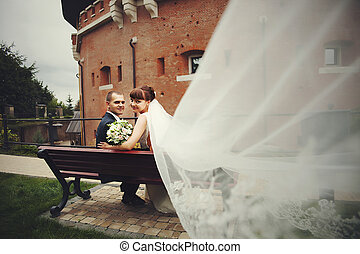 A look from bride's veil on the happy wedding couple sitting on the bench