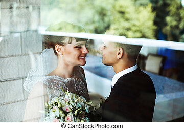 A look through the glass on a pretty bride with brunette hair smiling to a groom