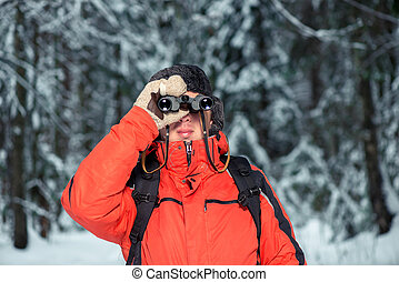a lost tourist man in a winter forest with binoculars