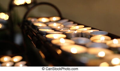 A lot of burning candles putten on a row in a church.