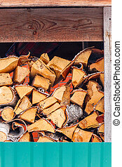 A lot of chopped firewood lies in a woodpile as fuel for a stove or fireplace.