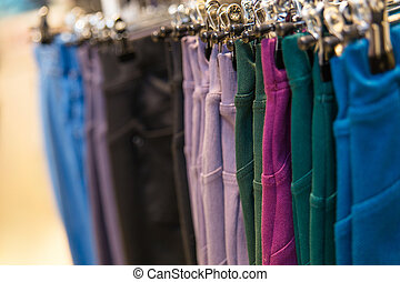 A lot of colored denim pants hanging on hangers in a clothing store.