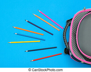A lot of colored pencils and a school bag on blue background. The view from the top.