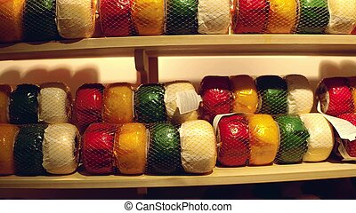 A lot of colorful cheese on factory shelf in the Netherlands