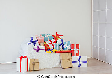 A lot of colorful gifts on the sofa in the interior of the white room