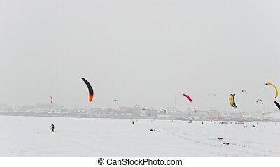 A lot of colorul snow-kites on the ice river in front of city at blizzard cloudy day, winter extremal sport