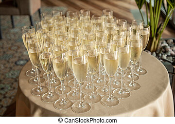 A lot of glasses with champagne on the table. Buffet table with glasses of champagne.