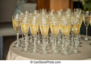 A lot of glasses with champagne on the table