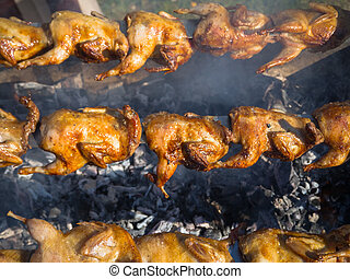 A lot of grilled chicken is roasted on a spit in the smoke.