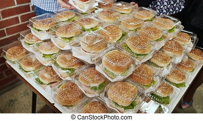 A lot of hamburgers in the form of a pyramid people dismantled at a party. Lunch break.