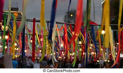 A lot of multicolored stripes with lamps hanging on the street in summer